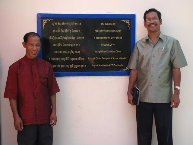 Pastor Vin and Barnabas Mam by the recognition plaque
